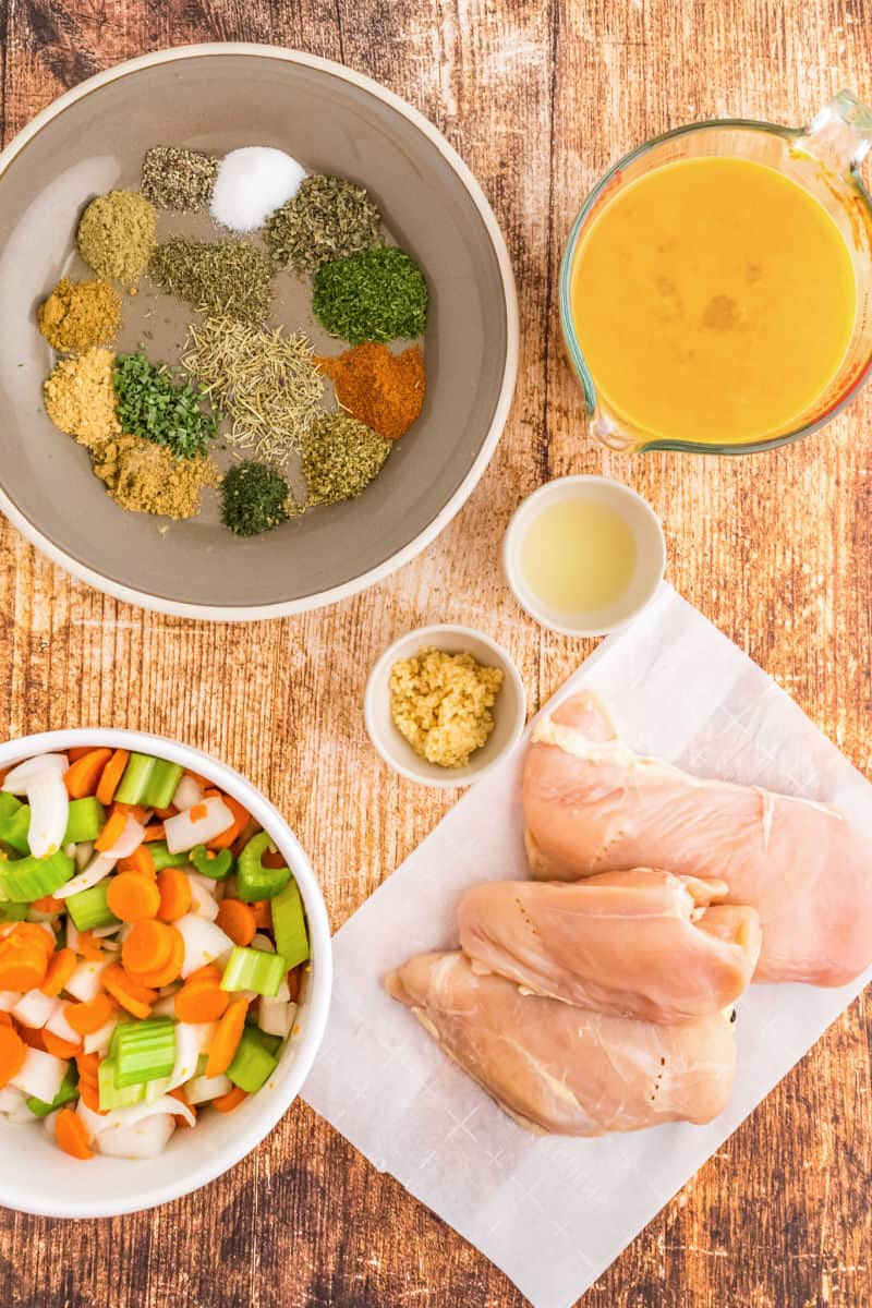 ingredients to make crockpot chicken noodle soup laid on on a tabletop
