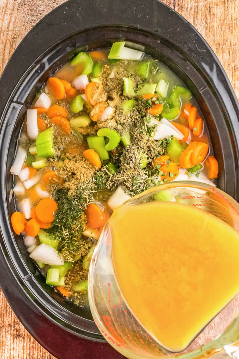 ingredients for chicken noodle soup in a crock pot with broth being poured in