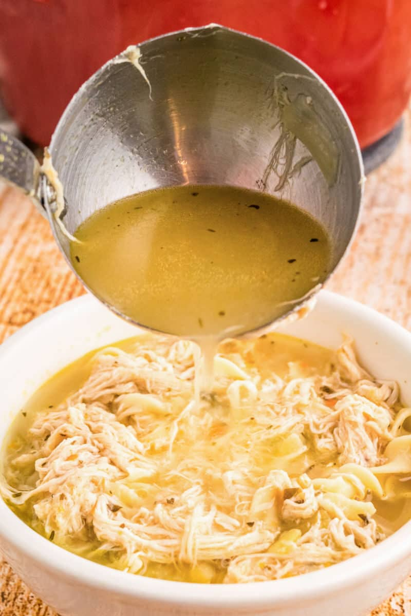 broth being ladled into a bowl of chicken noodle soup