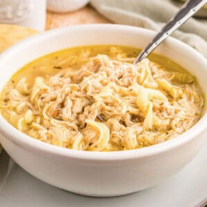 square image of crock pot chicken noodle soup in a bowl with a spoon