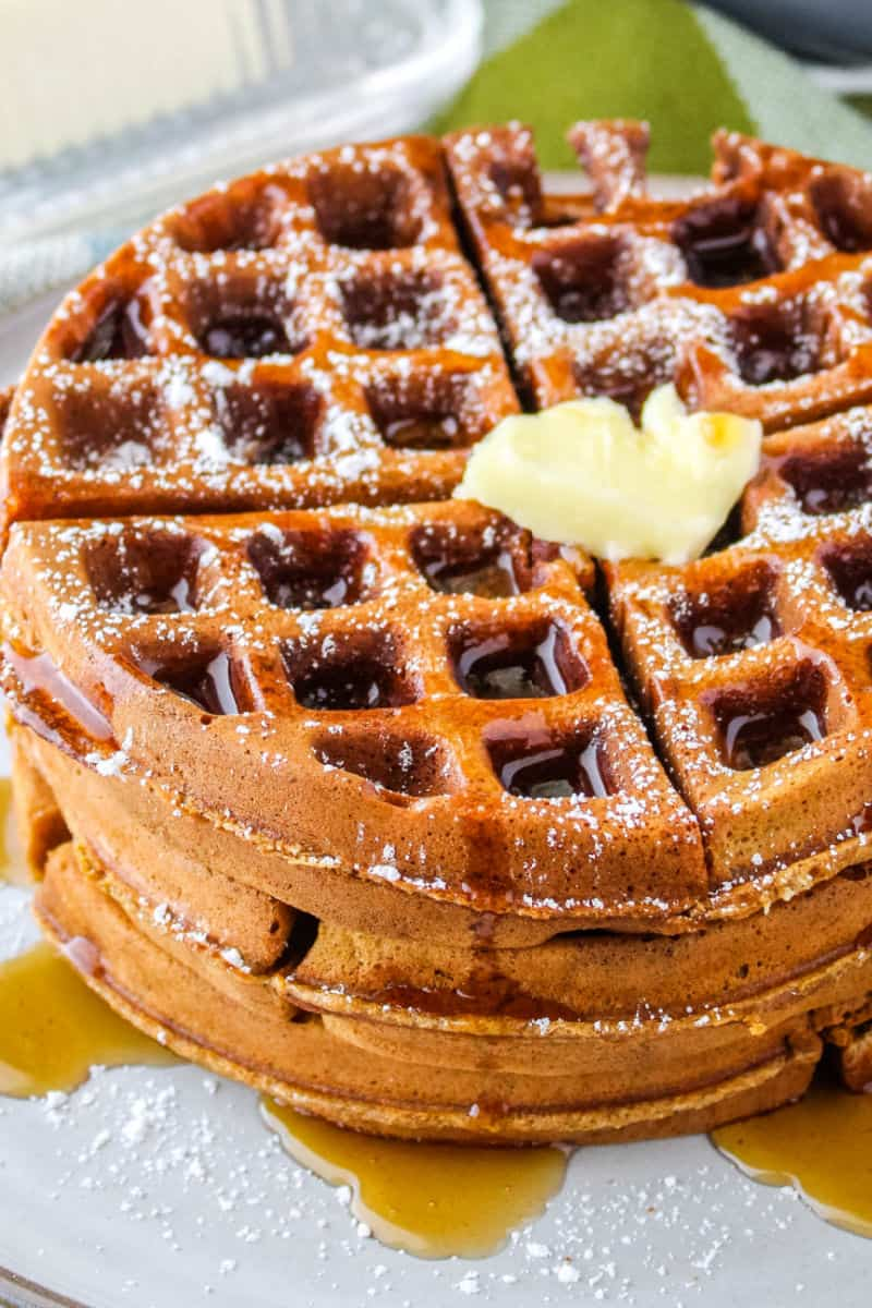 close up of gingerbread waffles topped with butter, syrup, and powdered sugar