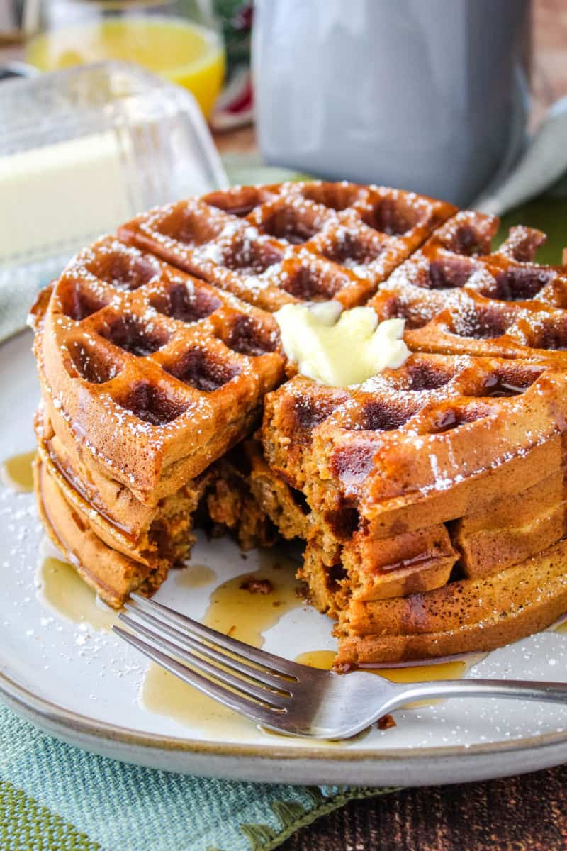 stack of gingerbread waffles on a plate with a fork and a portion cut out