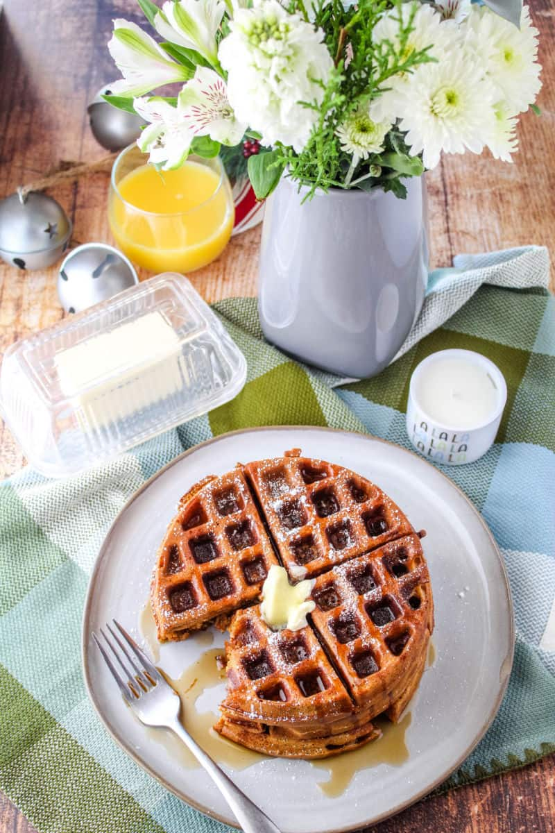 looking down at a breakfast setting with flowers, orange juice, butter dish, and waffles on a plate with a fork