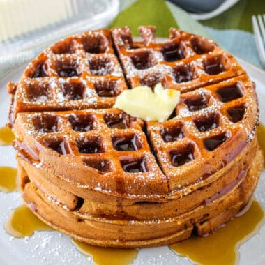 square image of a stack of gingerbread waffles with butter and syrup