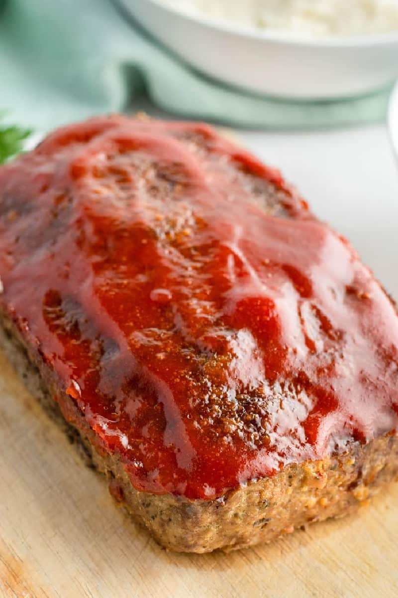 cooked meatloaf topped with glaze on a cutting board