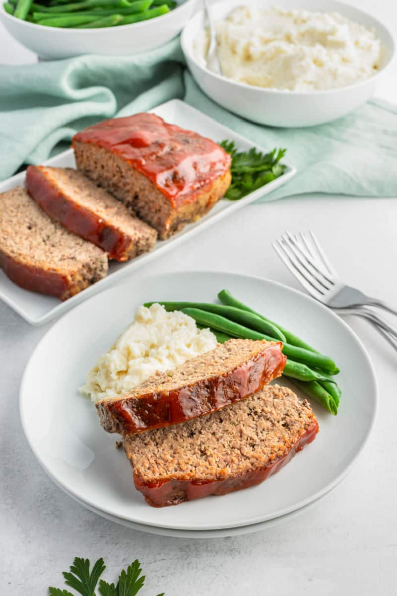 two slices of meatloaf on a plate with mashed potatoes and green beans