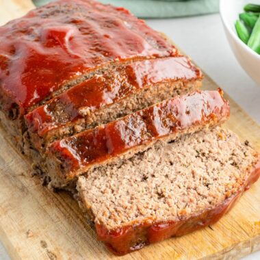 square image of meatloaf on a cutting board with a few slices cut
