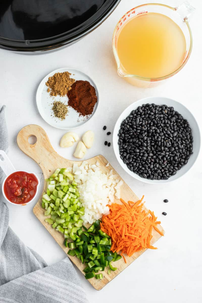 ingredients to make black bean soup laid out on a countertop next to a slow cooker