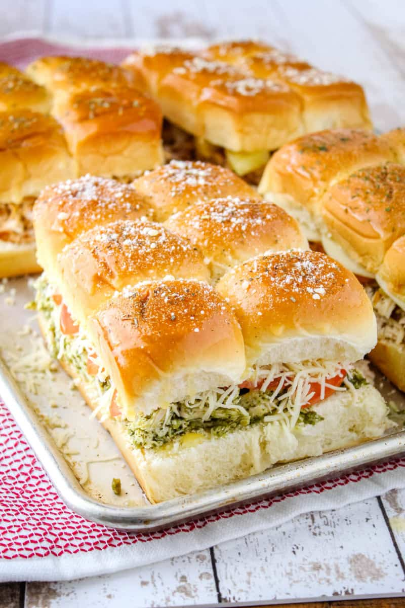 pest chicken sliders on a baking sheet with other types of slider showing toppings on rolls