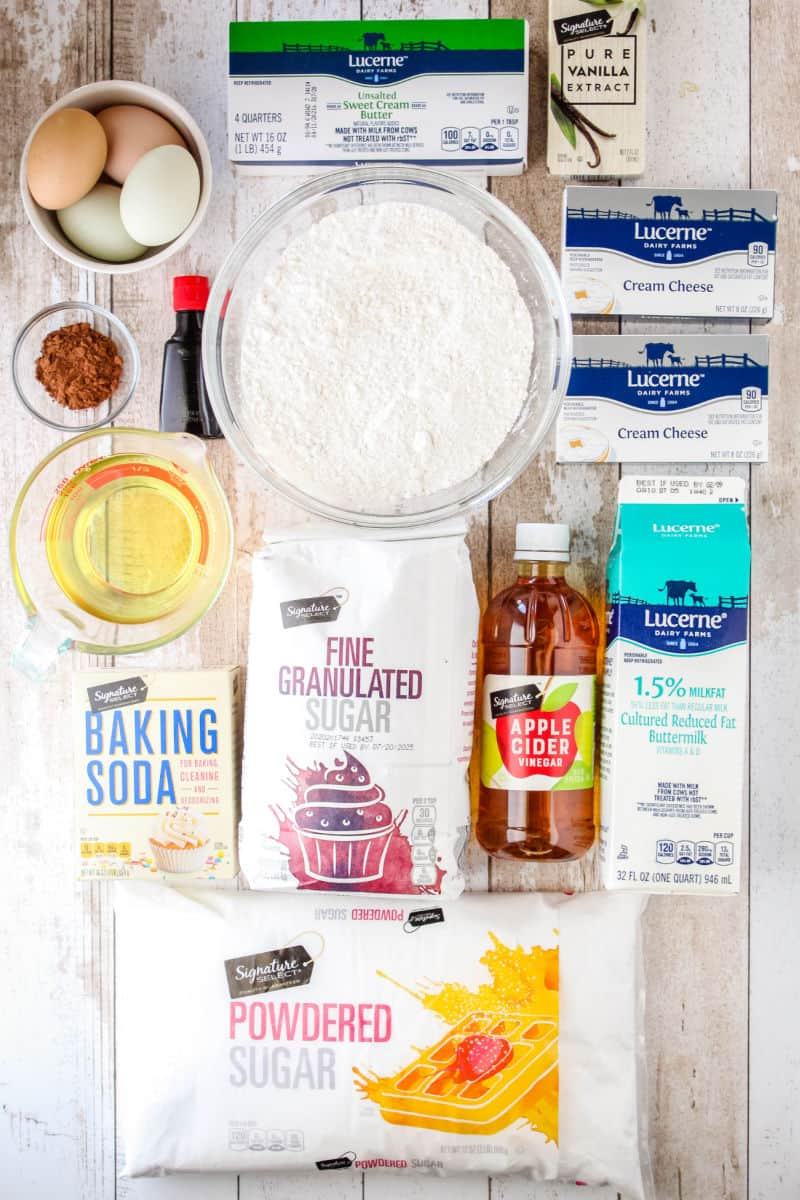 ingredients to make red velvet cake and cream chees frosting laid out on a tabletop