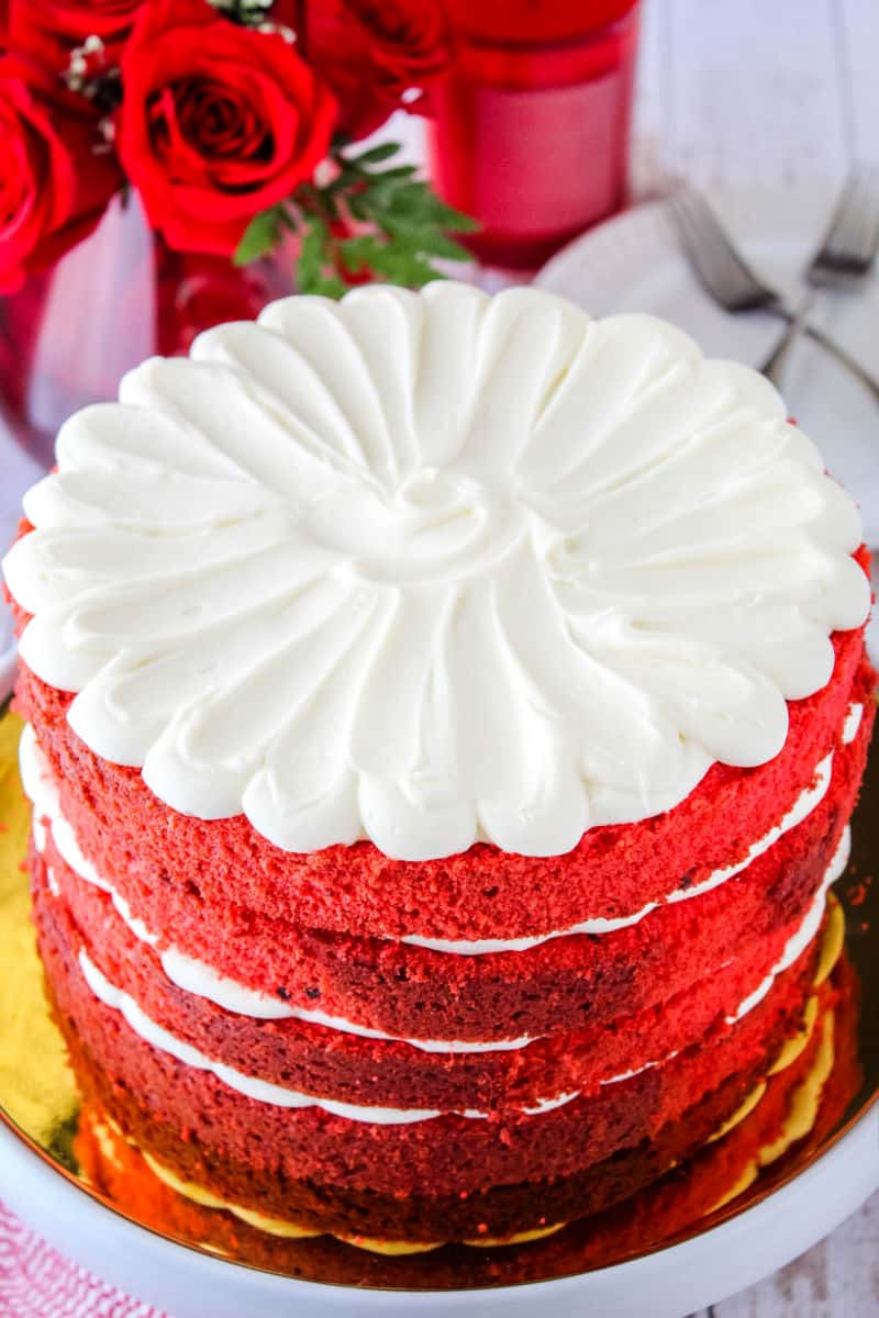 red velvet cake on a cake stand next to red roses, candle, plates, and forks