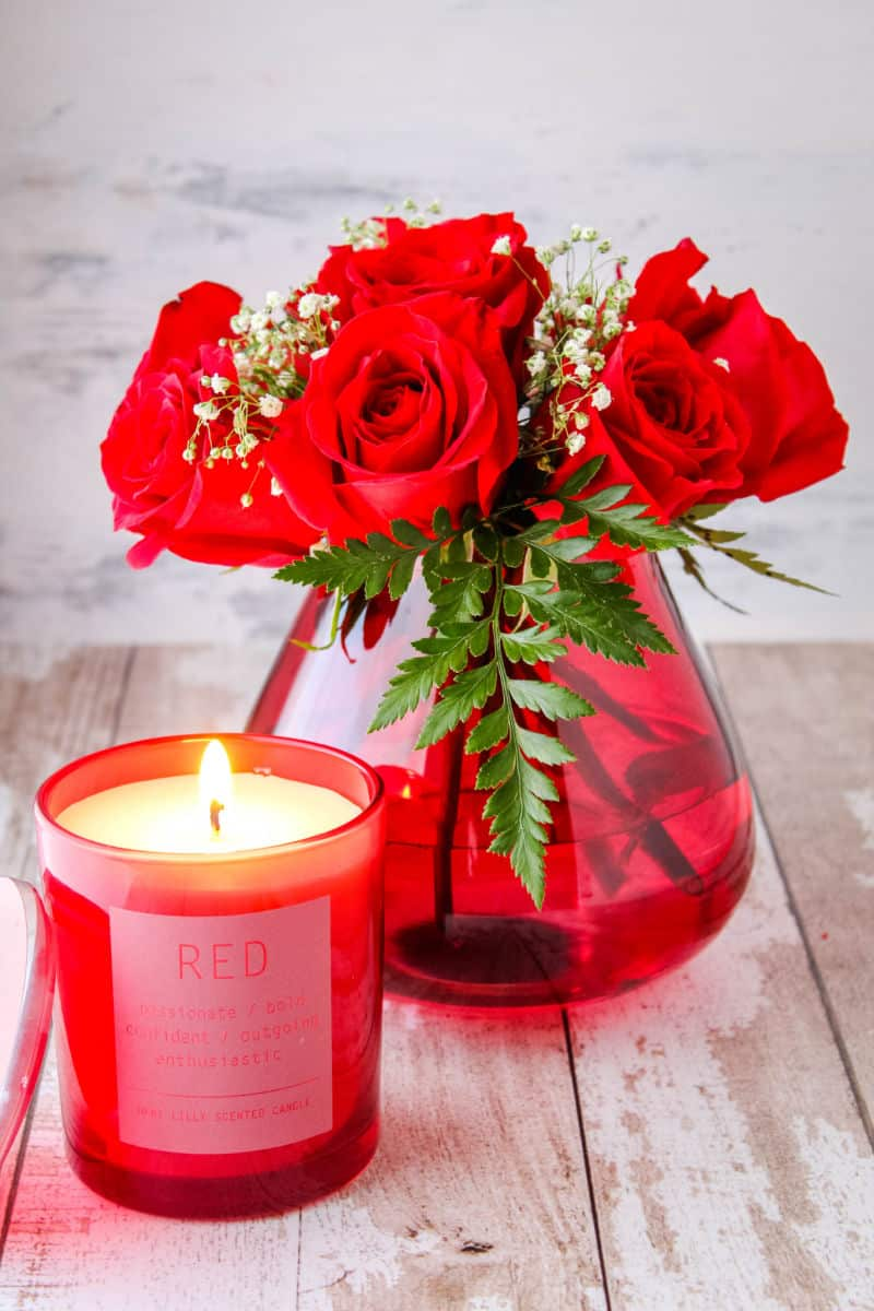 small bouquet of red roses in a red teardrop vase next to a red candle