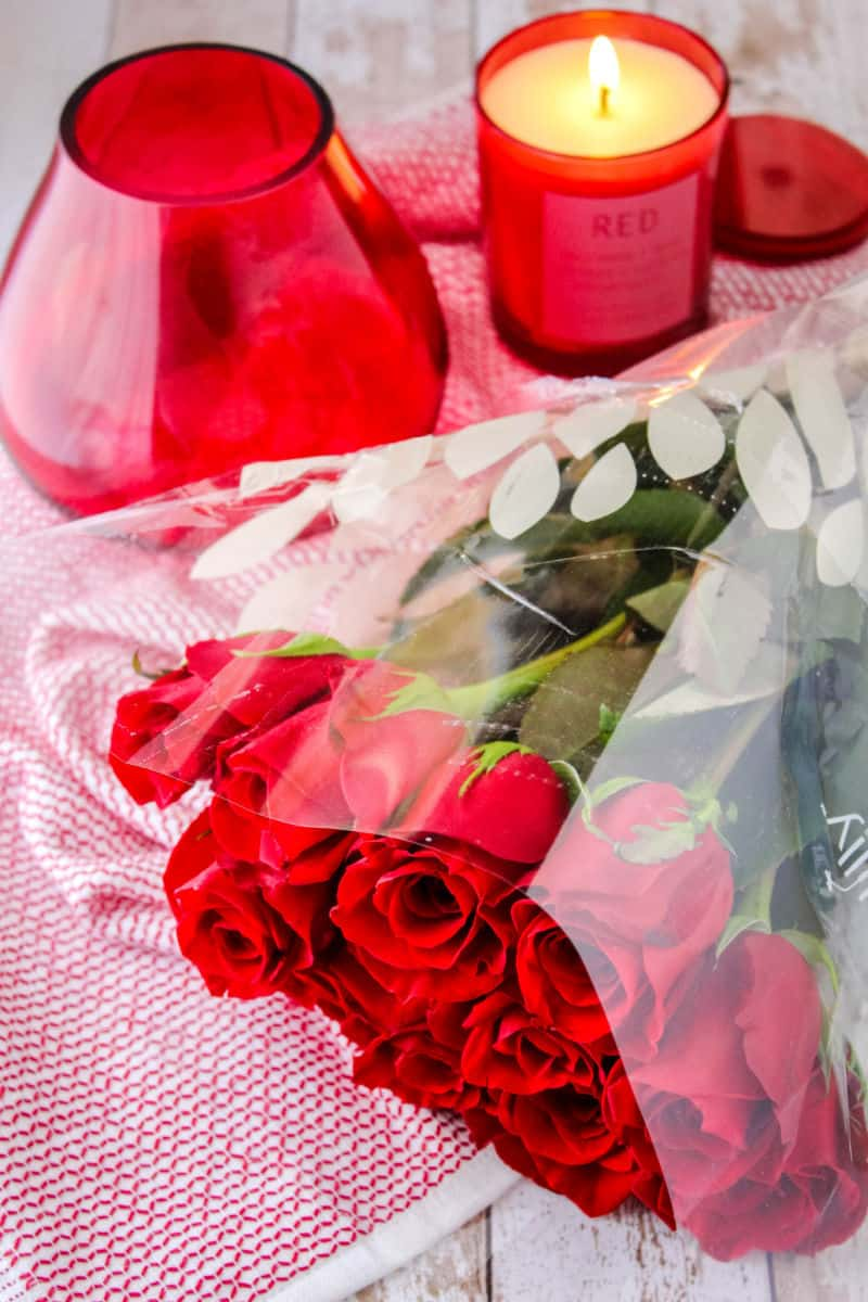 red teardrop fower vase, bouquet of red roses and a red candle