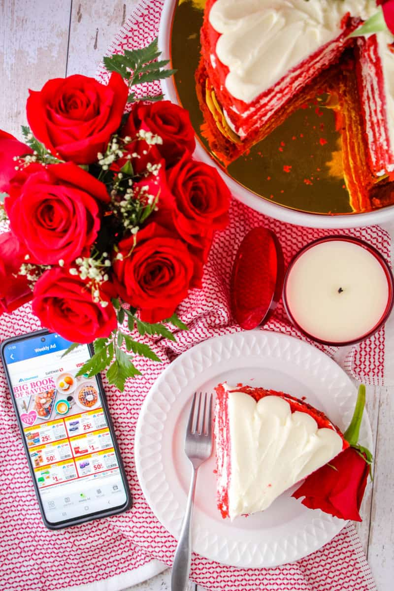 looking down at a bouquet of roses, slice of red velvet cake on a plate with a fork and a rose, a red candle, and smartphone with Albertsons app opened up