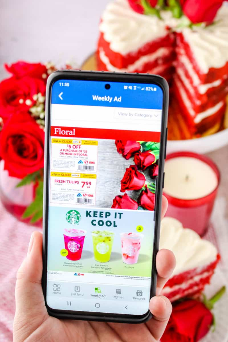 hand holding a smartphone showing floral coupons in Albertsons app