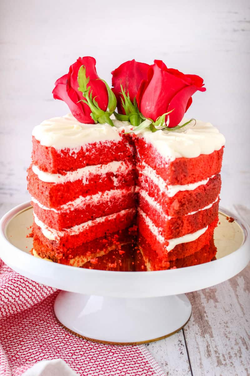 red velvet cake on a cake stand topped with fresh roses with a slice cut out to show layers