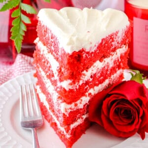 square image of a red velvet cake splice on a plate with a fork and rose