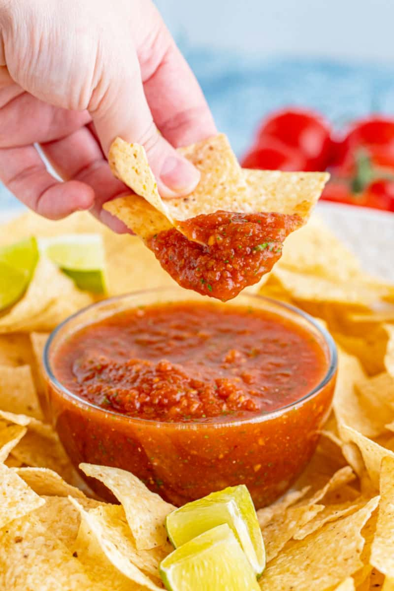 hand holding chips above a bowl of homemade salsa after dipping