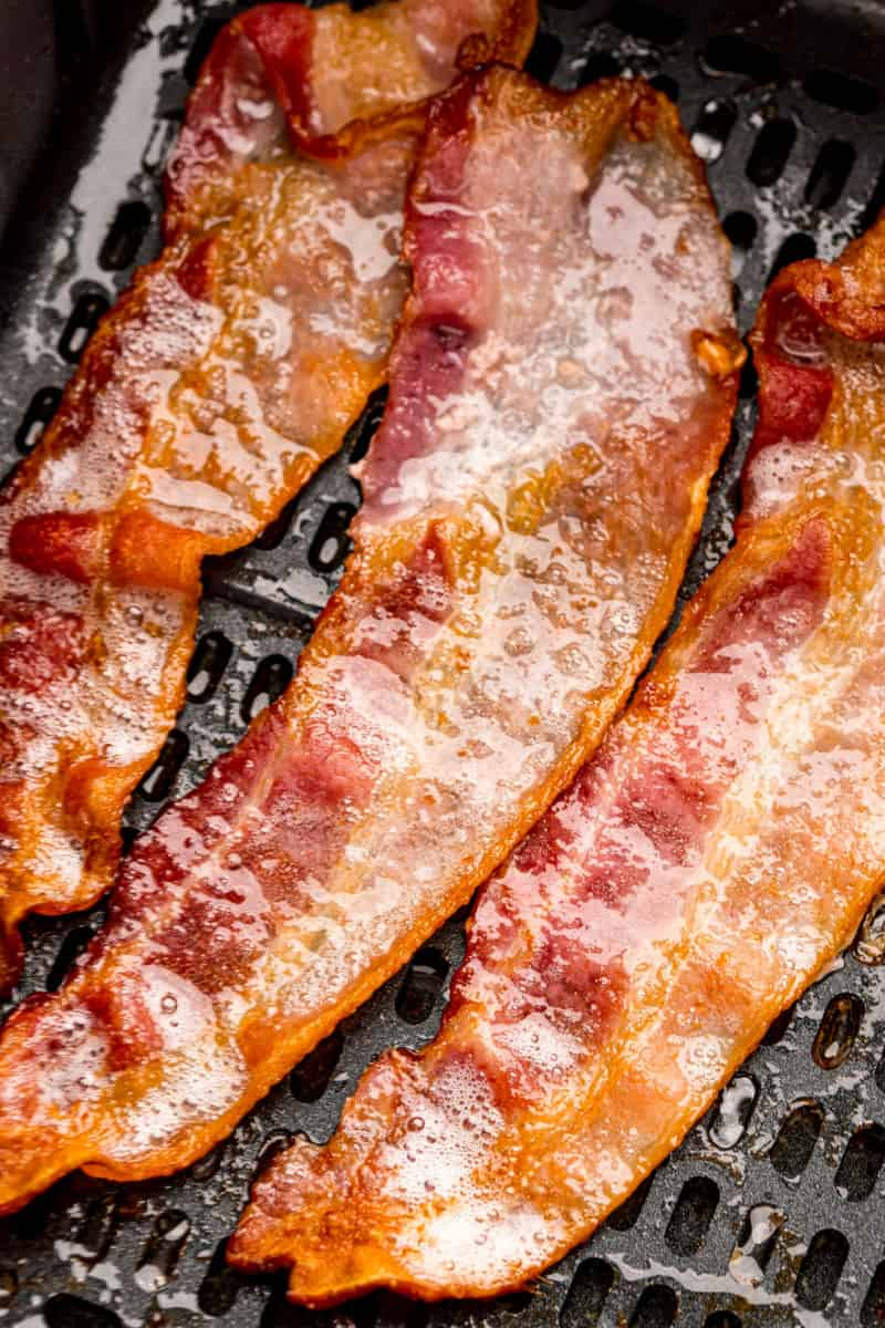 close up of strips of bacon in an air fryer basket halfway through cooking
