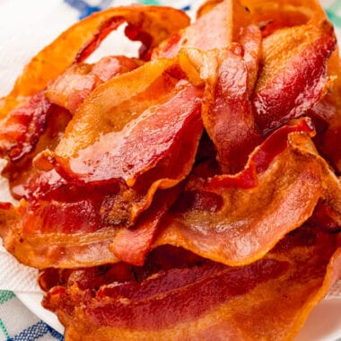 square image of air fryer bacon piled up on a plate