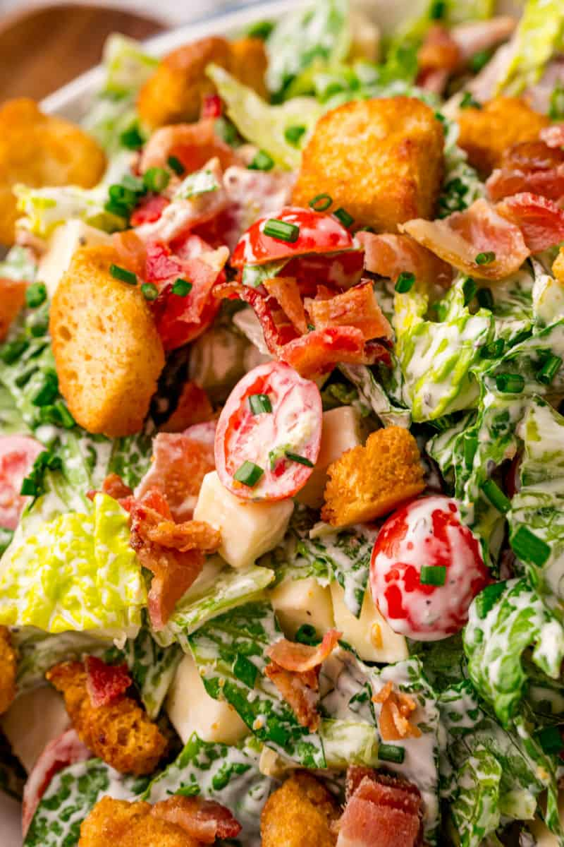 close up of BLT salad with croutons, tomatoes, bacon, and dressing