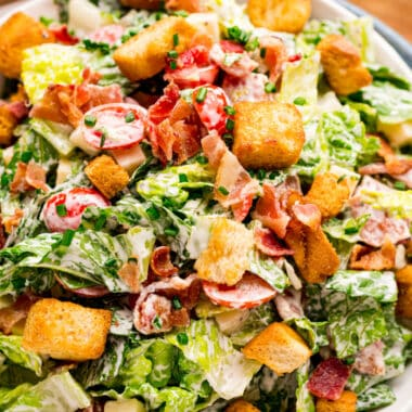 square close up image of BLT salad tossed in dressing