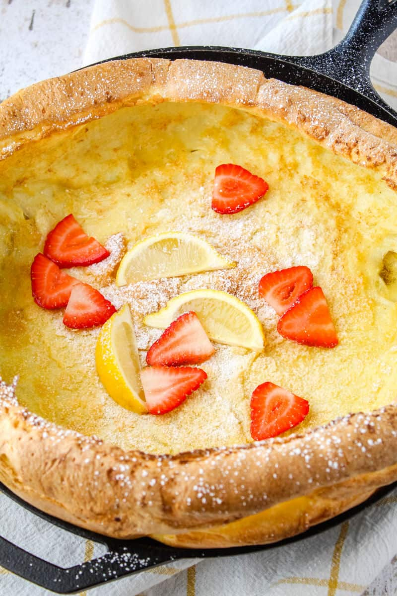dutch baby with powdered sugar, sliced strawberries, and lemon wedges on to