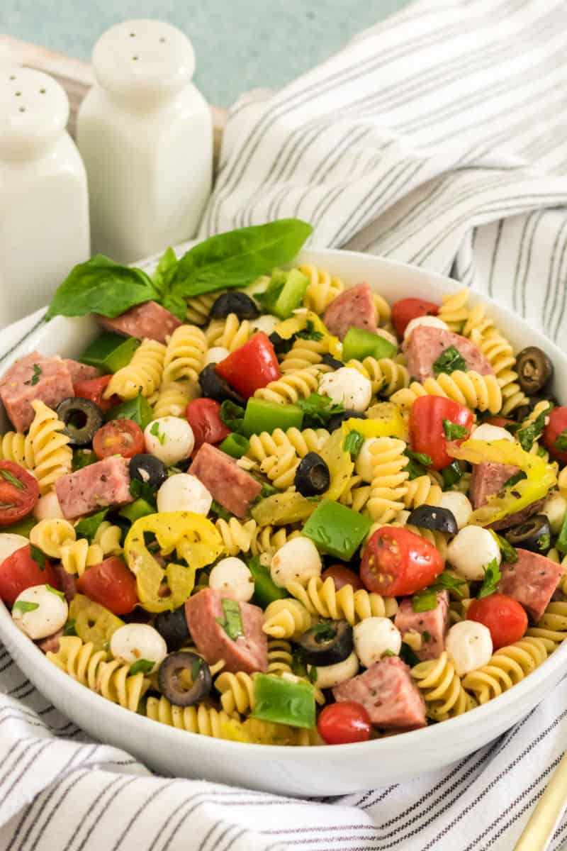 antipasto pasta salad on a serving tray next to salt and pepper shakers