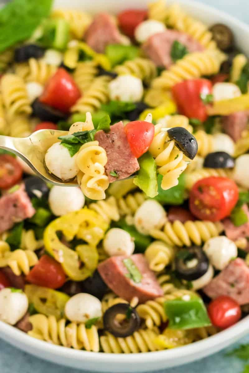 close up of antipasto pasta salad on a fork over the serving bowl