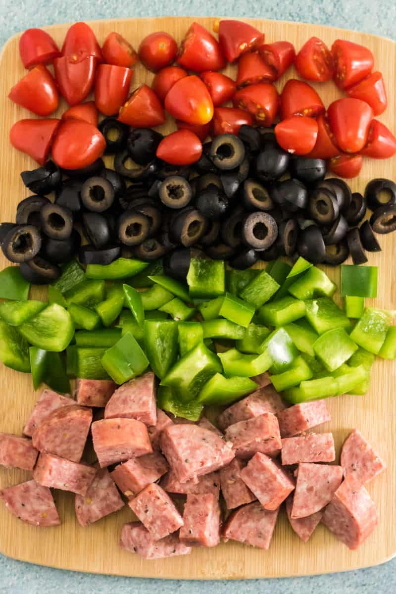 halved cherry tomatoes, sliced black olives, chopped green peppers, and diced summer sausage on a cutting board