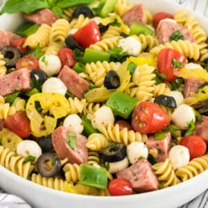 square close up image of antipasto pasta salad in a white bowl