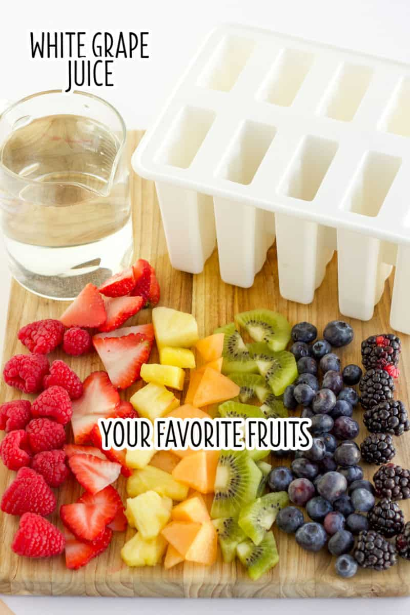 white grap juice in a carafe next to a popsicle mold and chopped fruit on a cutting board with text overlay