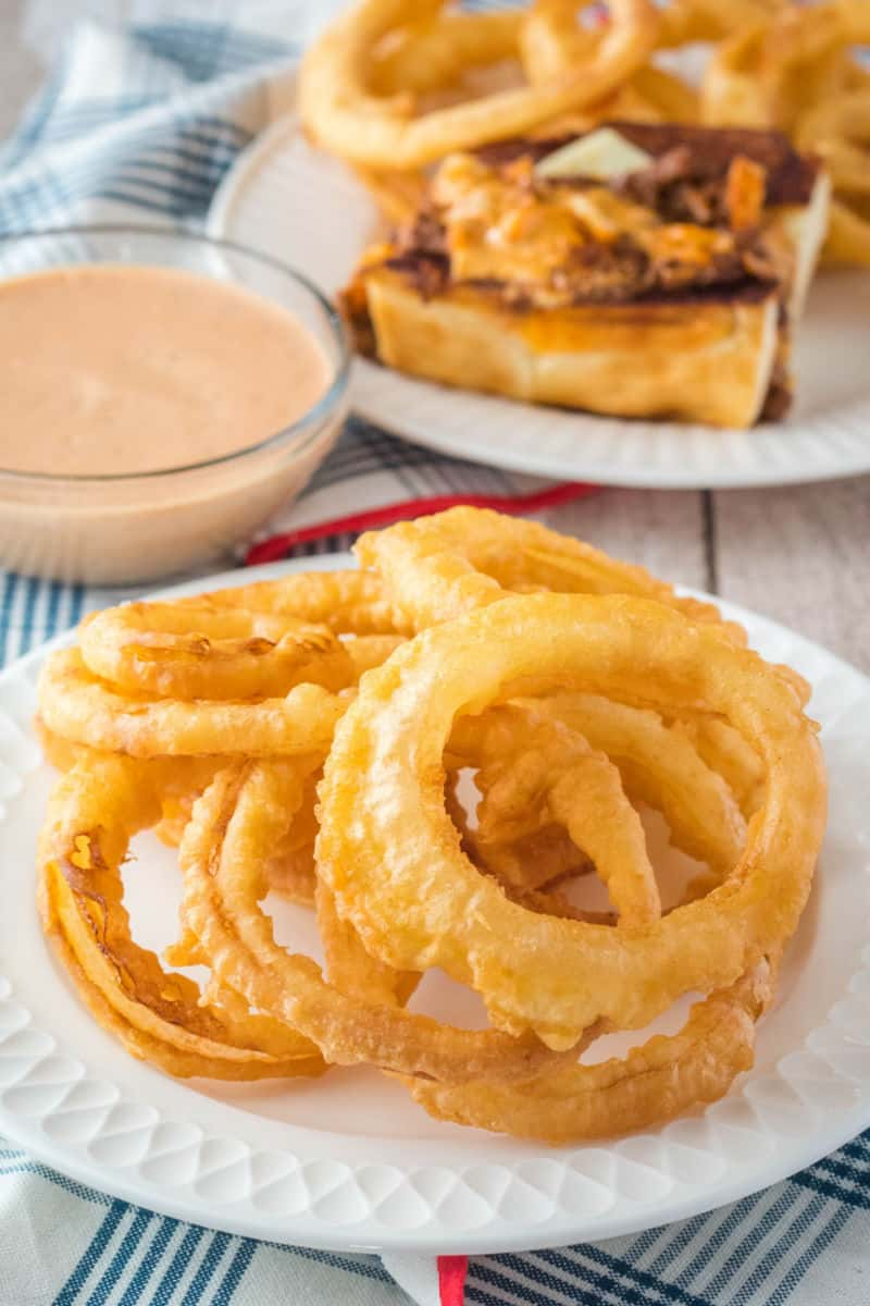 onion rings on a plate next to a bowl of fry sauce with a chili dog in the background