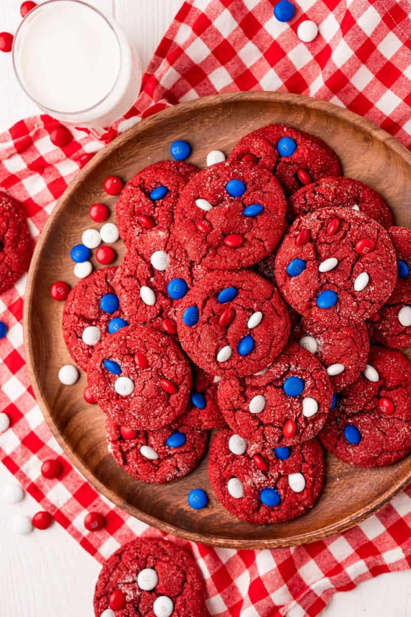 platter of red velvet cookies next to glass of milk