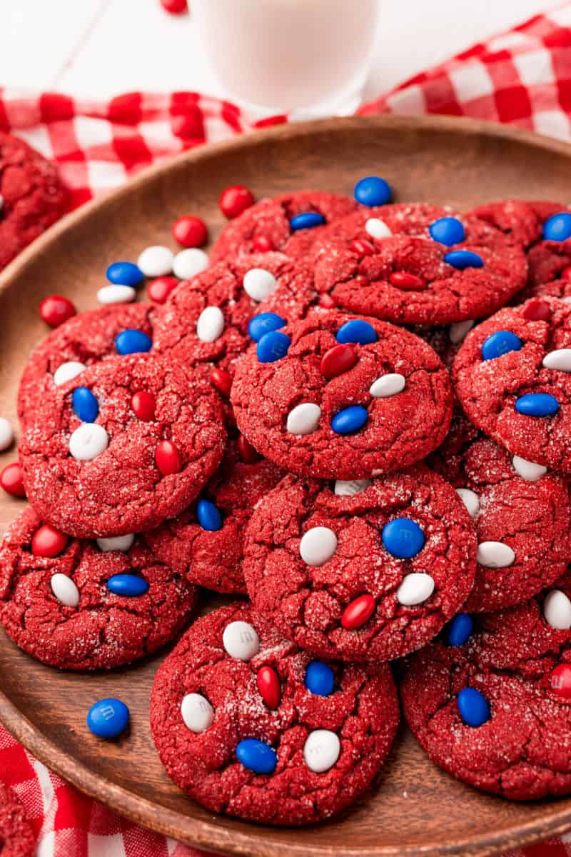 side view of red velvet cake mix cookies piled up on a wood plate
