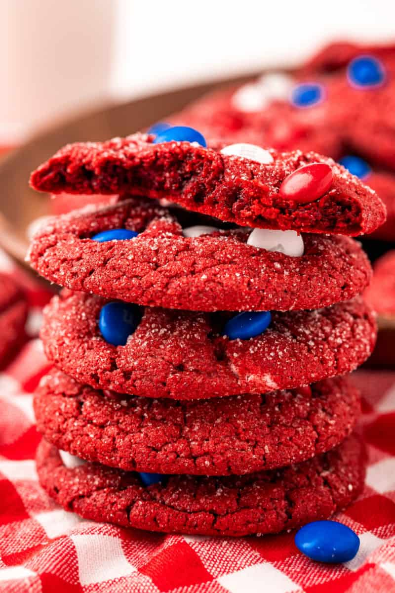 stack of red velvet cookies with a bite taken out of the top cookie