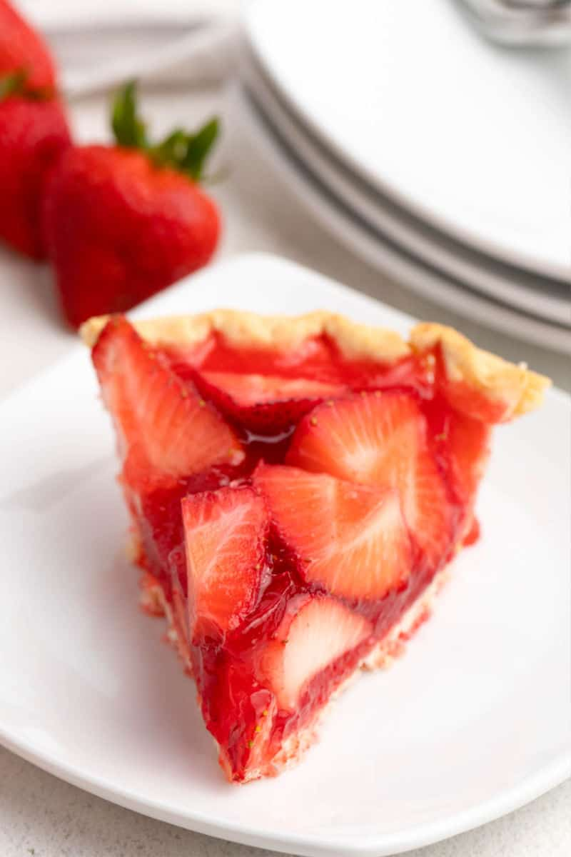 slice of strawberry pie on a plate with frehs strawberries in the background