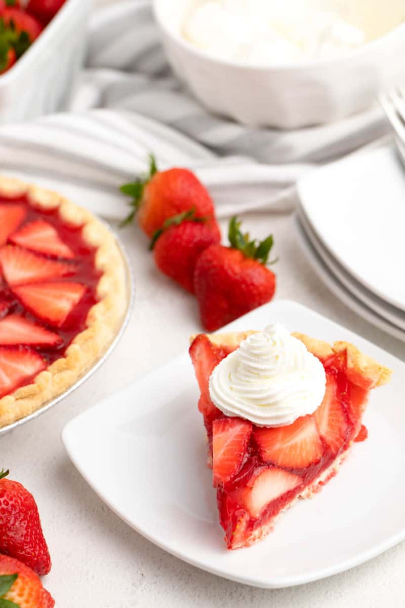 slice fo strawberry pie with whipped cream on top next to the rest of the pie