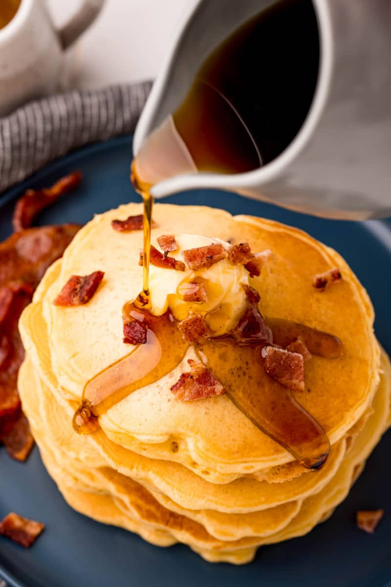 maple syrup being poured over bacon pancakes