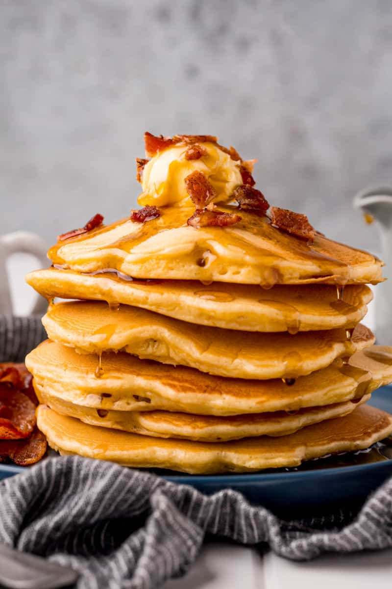 a stack of bacon pancakes on a plate with maple syrup dripping down the sides
