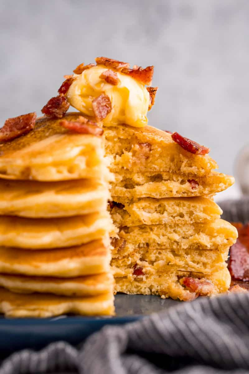 stack of bacon pancakes with a section cut out to show the insides