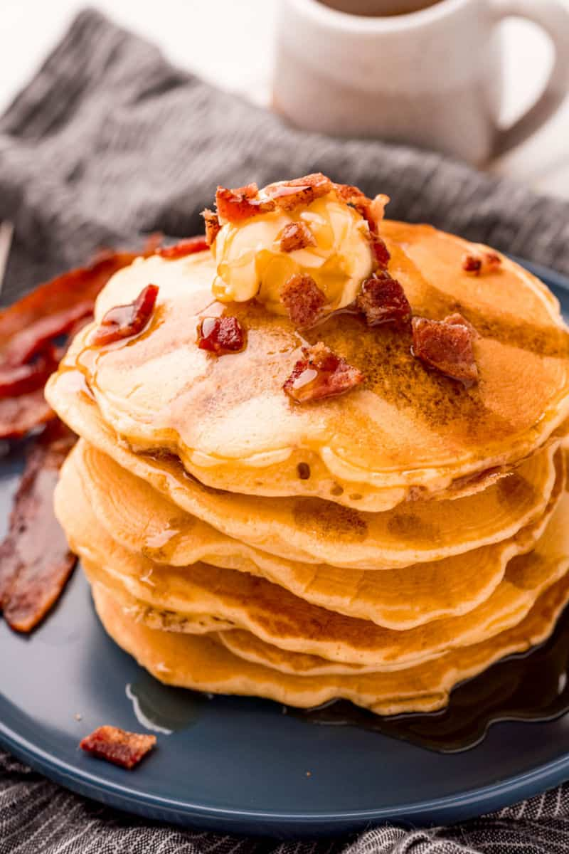 stack of bacon pancakes topped with butter, crumbled bacon, and maple syrup