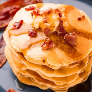 square image of bacon pancakes with butter, syrup, and crumbled bacon on top