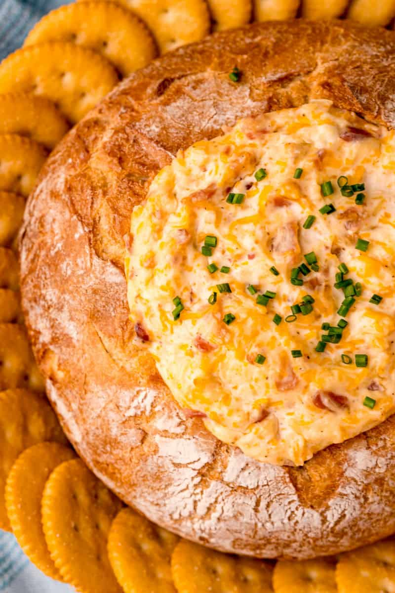 mississippi sin dip in a bread bowl on a platter with Ritz crackers