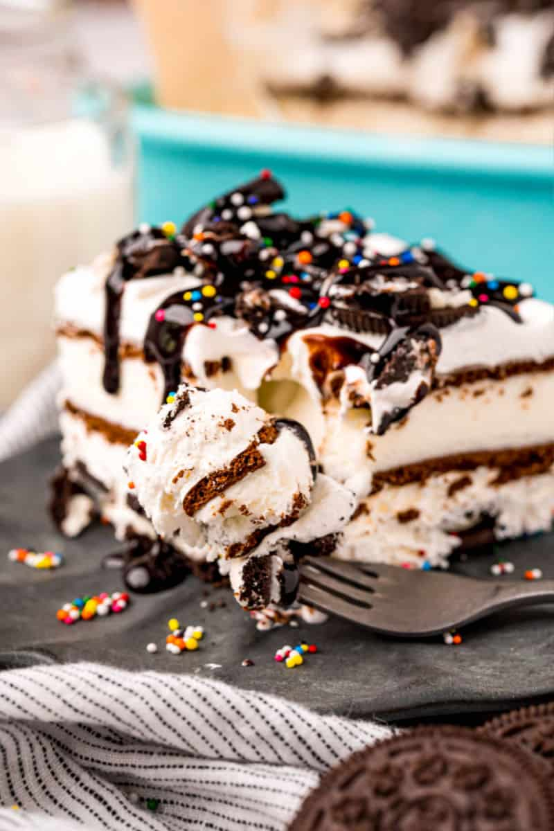bite of oreo ice cream sandwich cake on a fork next to a slice