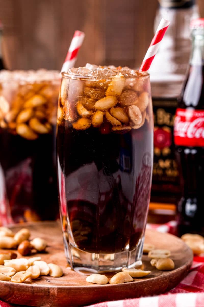 close up of peanuts and coke with bourbon next to coke and bourbon bottles