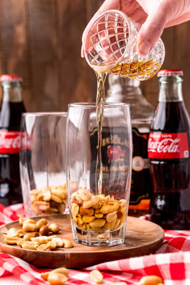 bourbon being poued into a glass with peanuts in the bottom
