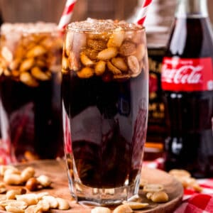 square image of peanuts and coke in glasses with straws