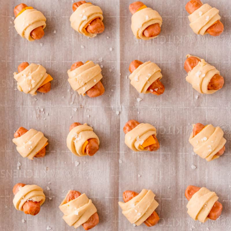 cheddar pigs in a blanket on a baking sheet with parchment paper before baking