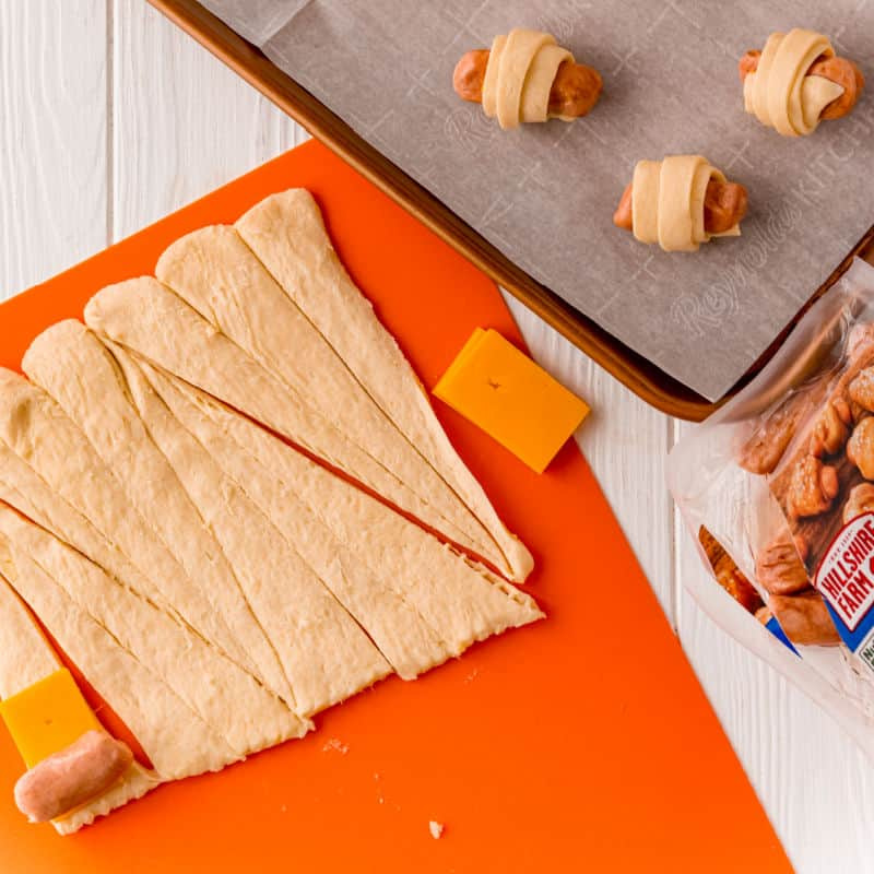lil' msokies and cheddar cheese slices placed on crescent roll triangles to make cheddar pigs in a blanket